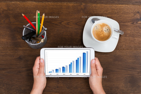 Person Showing Graph On Mobile Phoneの写真素材 [FYI00783245]