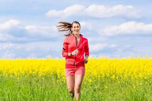 Frau beim Jogging Sport vor Rapsfeld in Fr?hlingの写真素材 [FYI00783247]