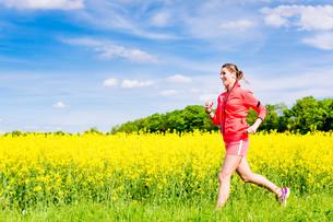 Frau beim Jogging Sport vor Rapsfeld in Fr?hlingの写真素材 [FYI00783249]