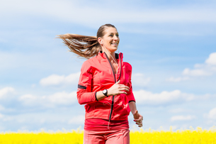 Frau beim Jogging Sport vor Rapsfeld in Fr?hlingの写真素材 [FYI00783250]