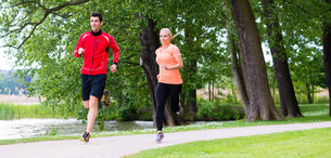woman and man jogging on forest path outdoorsの写真素材 [FYI00783297]