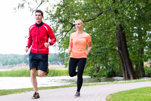 woman and man jogging on forest path outdoorsの写真素材 [FYI00783314]