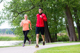 woman and man jogging on forest path outdoorsの写真素材 [FYI00783315]