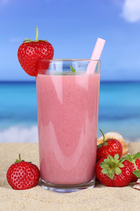 strawberry smoothie juice cocktail with strawberry fruit juice on the beachの写真素材 [FYI00783358]