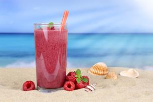 raspberry smoothie juice cocktail with raspberry fruit juice on the beachの写真素材 [FYI00783381]