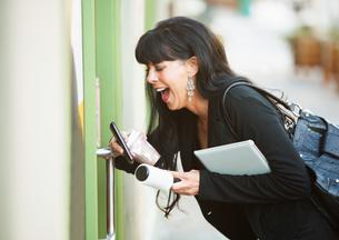 Multitasking Woman Opening Doorの写真素材 [FYI00783382]