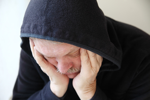 Sad older man in hooded jacketの写真素材 [FYI00783407]