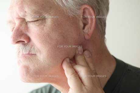 Man suffering from jaw joint painの写真素材 [FYI00783419]