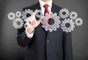 Businessman with gears, concept of well organized work process.の写真素材 [FYI00783529]