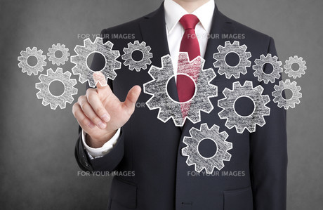 Businessman with gears, concept of well organized work process.の写真素材 [FYI00783530]