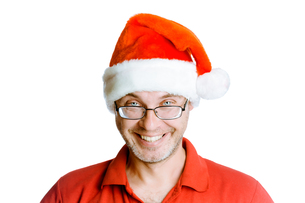 Smiling happy unshaven man with glasses and a hat Santaの写真素材 [FYI00783914]
