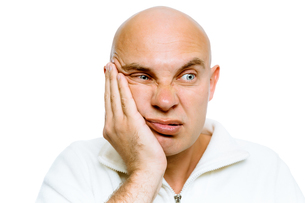 man holding his hand to his cheek. Toothache or problemの写真素材 [FYI00783924]