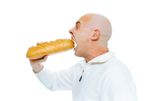 man biting a loaf. Isolated on white. Profileの写真素材 [FYI00783941]