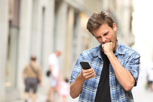 furious angry man watching mobile phoneの写真素材 [FYI00783961]