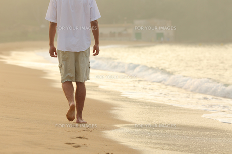 Man walking and leaving footprints on the sand of a beachの素材 [FYI00783965]