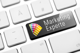 marketing expert button on white keyboard with color fansの写真素材 [FYI00784060]