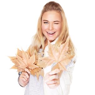 Joyful girl with dry leavesの写真素材 [FYI00784687]