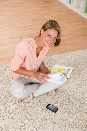 Woman With Diary Sitting On Carpetの写真素材 [FYI00784799]