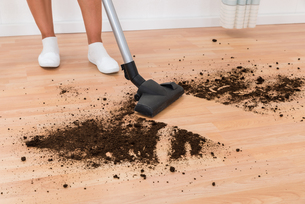 Person With Vacuum Cleaner Cleaning Floorの写真素材 [FYI00784855]