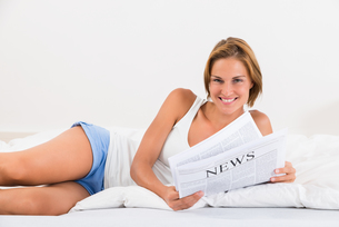 Woman In Bed With Newspaperの写真素材 [FYI00784862]