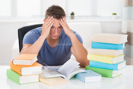 Tired Man Studying Booksの写真素材 [FYI00784865]