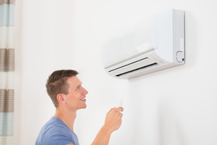 Man With Remote Control To Operate Air Conditionerの写真素材 [FYI00784866]