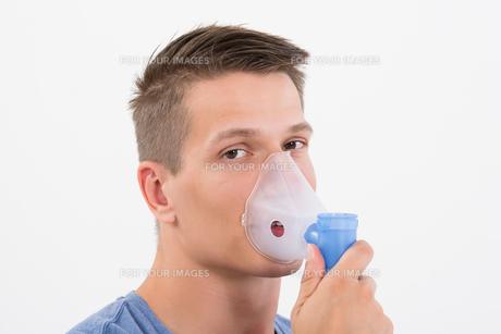 Man Inhaling Through Inhaler Maskの写真素材 [FYI00784869]