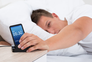 Man Snoozing Alarm Clock On Cell Phoneの写真素材 [FYI00784877]