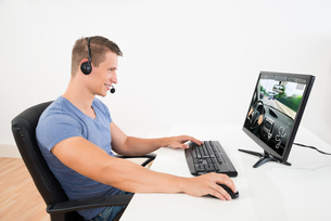 Man With Headset Playing Game On Computerの写真素材 [FYI00784888]