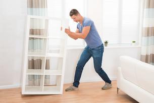 Young Man Moving Shelfの写真素材 [FYI00784894]