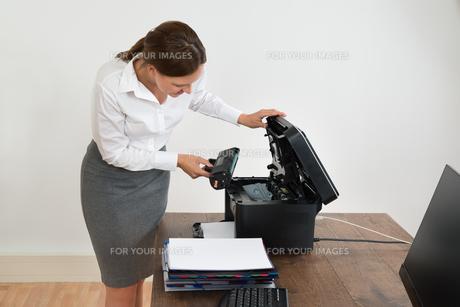 Businesswoman Putting Laser Toner Cartridge In Printerの写真素材 [FYI00784908]