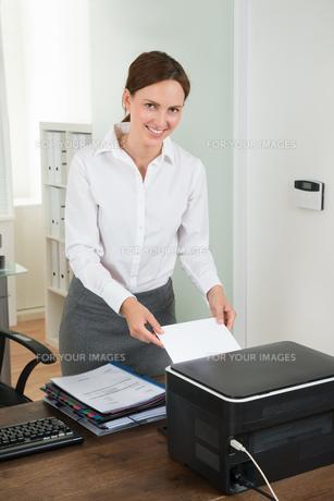 Secretary Inserting Paper In Printerの写真素材 [FYI00784914]
