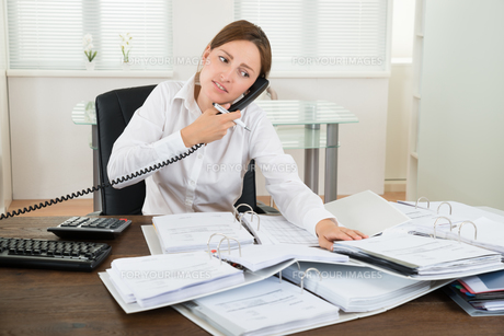 Businesswoman Using Telephone While Doing Accountingの写真素材 [FYI00784945]