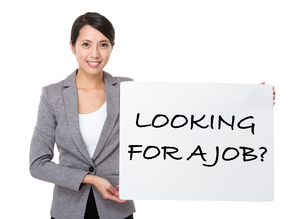 Beautiful businesswoman showing a placard showing with looking for a job phrasesの写真素材 [FYI00785121]