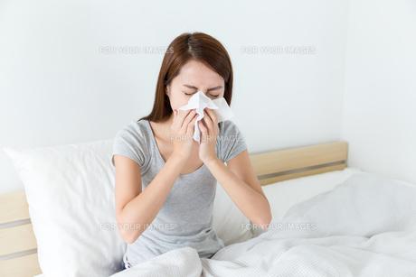 Asian woman feeling unwell and sneeze on bedの素材 [FYI00785137]