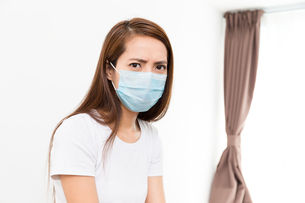 Asian woman wear with protective face mask at homeの写真素材 [FYI00785140]