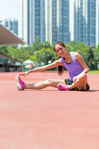 Woman doing warm up exercise in sport stadiumの写真素材 [FYI00785151]