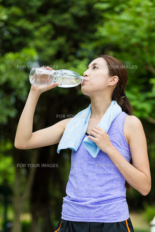 Asian woman drinking bottle of water after doing sport exerciseの写真素材 [FYI00785165]