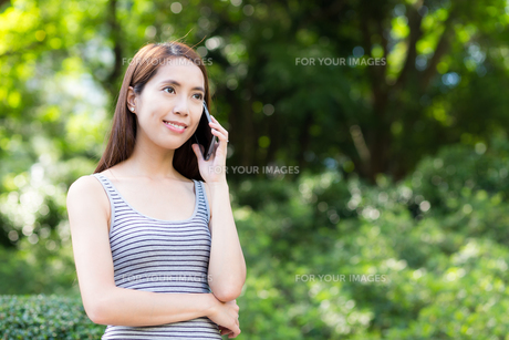 Asian woman talk to cellphone at parkの写真素材 [FYI00785168]