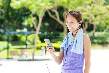 Sporty girl listen to music with smartphoneの写真素材 [FYI00785186]