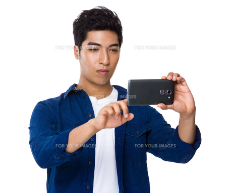 Iranian mixed man use of the cellphone for taking photoの写真素材 [FYI00785439]