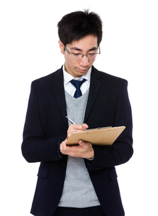 Young businessman write on clipboardの写真素材 [FYI00785736]