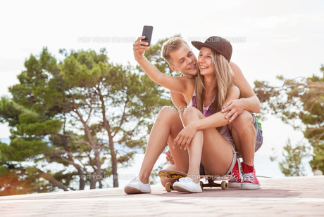 Happy couple with sitting on skateboard and taking a selfieの写真素材 [FYI00786106]