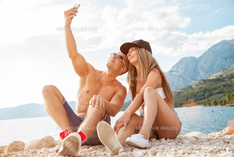 Couple sitting on a beach and taking a selfieの写真素材 [FYI00786111]