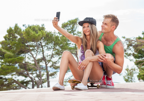 Happy couple with sitting on skateboard and taking a selfieの写真素材 [FYI00786123]