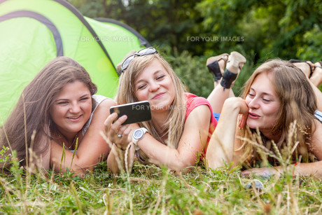 Group of friends outdoors with a smart phoneの写真素材 [FYI00786125]