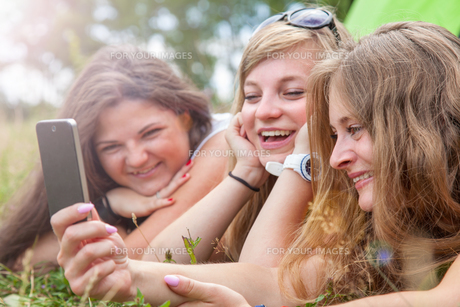 Group of friends outdoors with a smart phoneの写真素材 [FYI00786136]