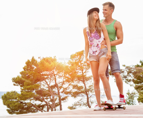 Young happy couple with a skateboardの写真素材 [FYI00786138]