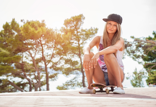 Young woman sitting on a skateboard outdoorsの写真素材 [FYI00786139]