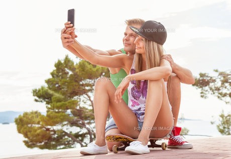 Happy couple with sitting on skateboard and taking a selfieの写真素材 [FYI00786143]